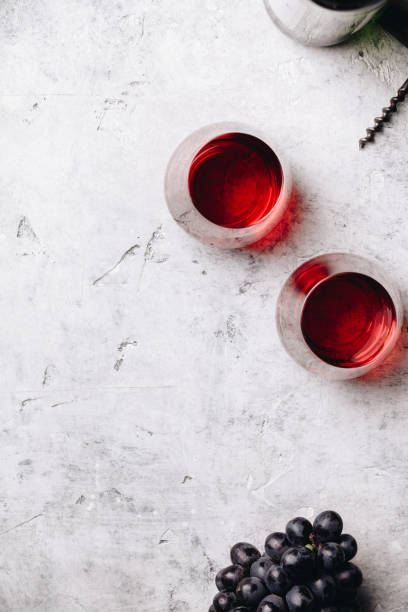 Glasses of red wine and grapes on rustic concrete background stock photo