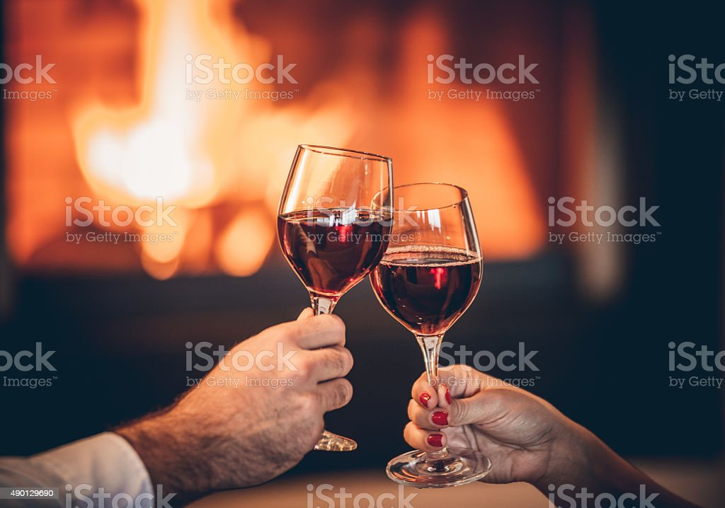 Glasses of red wine and romantic fireplace stock photo