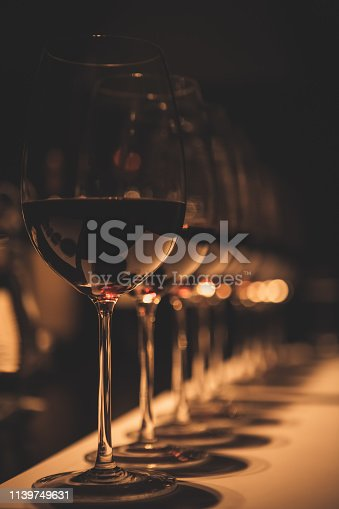 Several glasses of different kinds of red wine lined up in a dark, romantic wine tasting room.