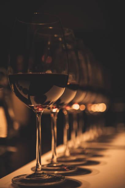 gläser rotwein in weinverkostungszimmer - französische land tisch stock-fotos und bilder