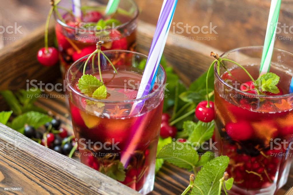 Glasses of refreshing  drink flavored with fresh fruit and decorated with cherries covered with dew drops. Wooden background stock photo