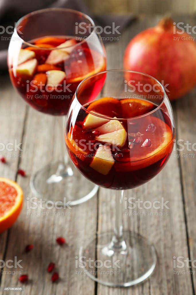 Glasses of sangria on wooden table with pomegranate stock photo