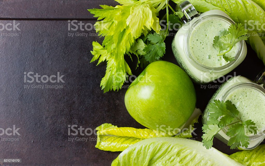 Glasses of smoothie, fresh green vegetables and fruits.  Top view stock photo