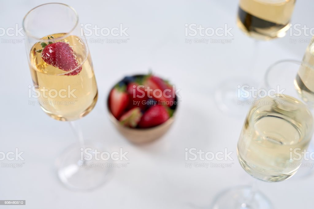 Glasses of sparkling wine with strawberry garnish on a table stock photo