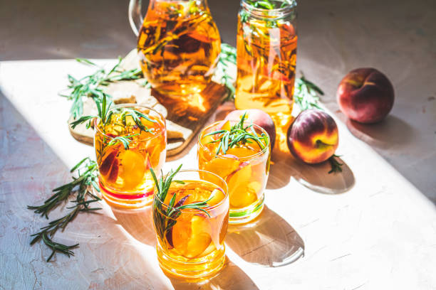 Glasses of sweet peach iced tea, Summer cold peach fizz cocktail with rosemary. Sunny light. Shallow depth of the field, close up, copy space for you text stock photo