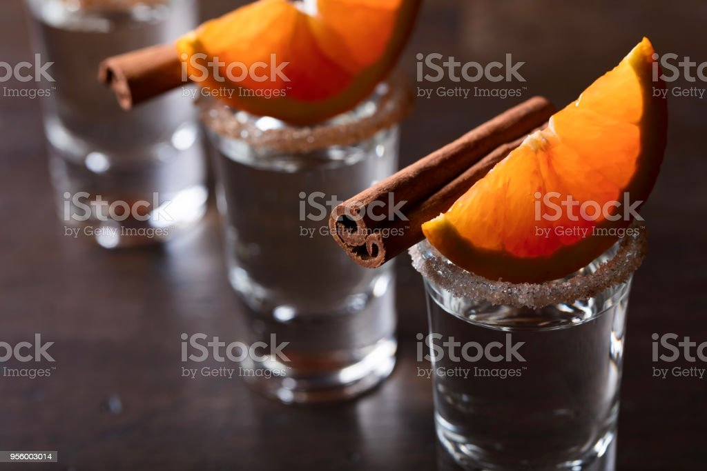 Glasses of tequila with orange and cinnamon sticks on a wooden table. stock photo