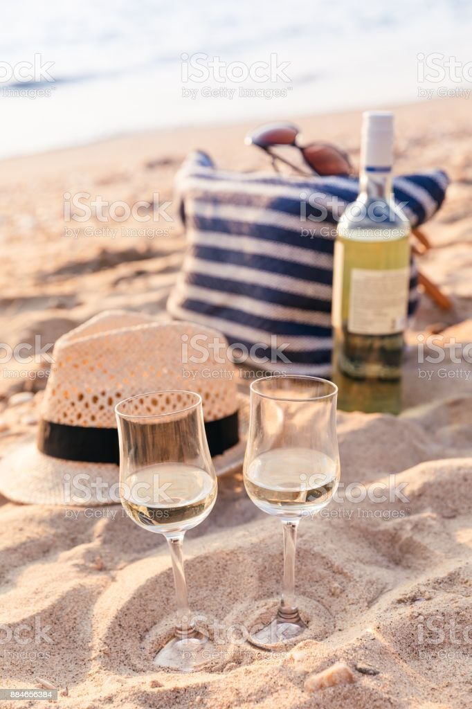 Glasses of the white wine on the sunset beach, picnic theme stock photo