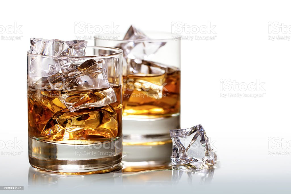 glasses of whiskey with ice cubes, background fades to white stock photo