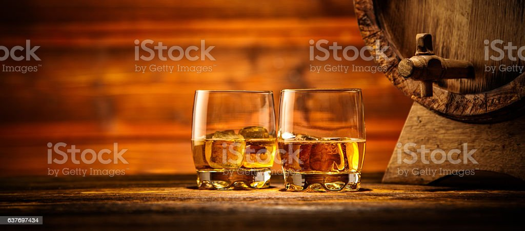 Glasses of whiskey with ice cubes served on wood stock photo