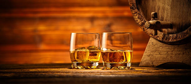 glasses of whiskey with ice cubes served on wood - whiskey stock photos and pictures