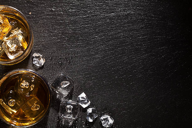 Verre de whisky avec de la glace sur la table en pierre noire - Photo