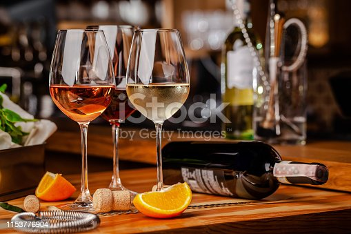 istock Glasses of white, rose and red wine are on the table, a bottle and corks are nearby. Glasses are on the table in the bar in the restaurant. Background image. copy space 1153776904