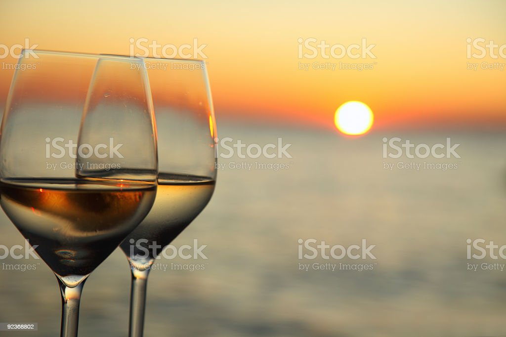 Glasses of wine against red sunset royalty-free stock photo