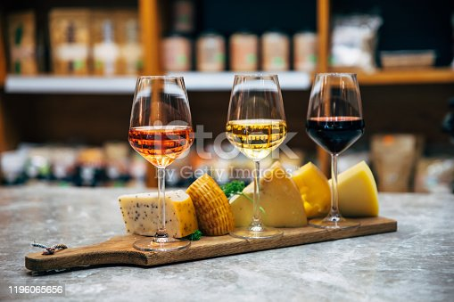 istock Glasses of Wine and cheese. Assortment or various type of cheese, wine glasses and bottles on the table in restaurant. Red, rose and yellow wine or champagne on the table. Winery concept image 1196065656