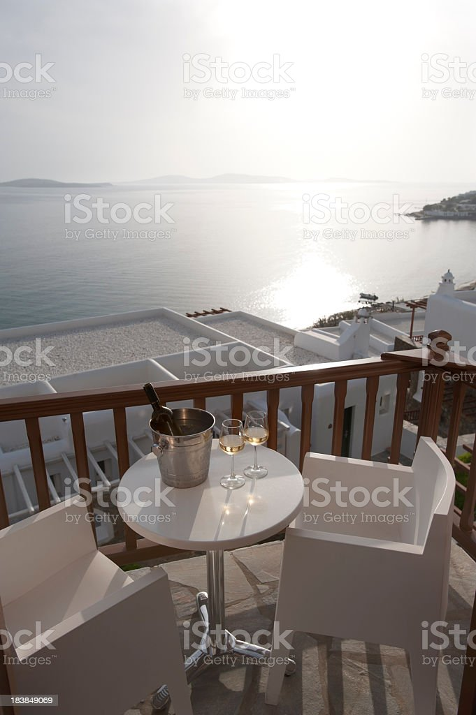 Glasses of wine with an ice bucket on a balcony overlooking the ocean...
