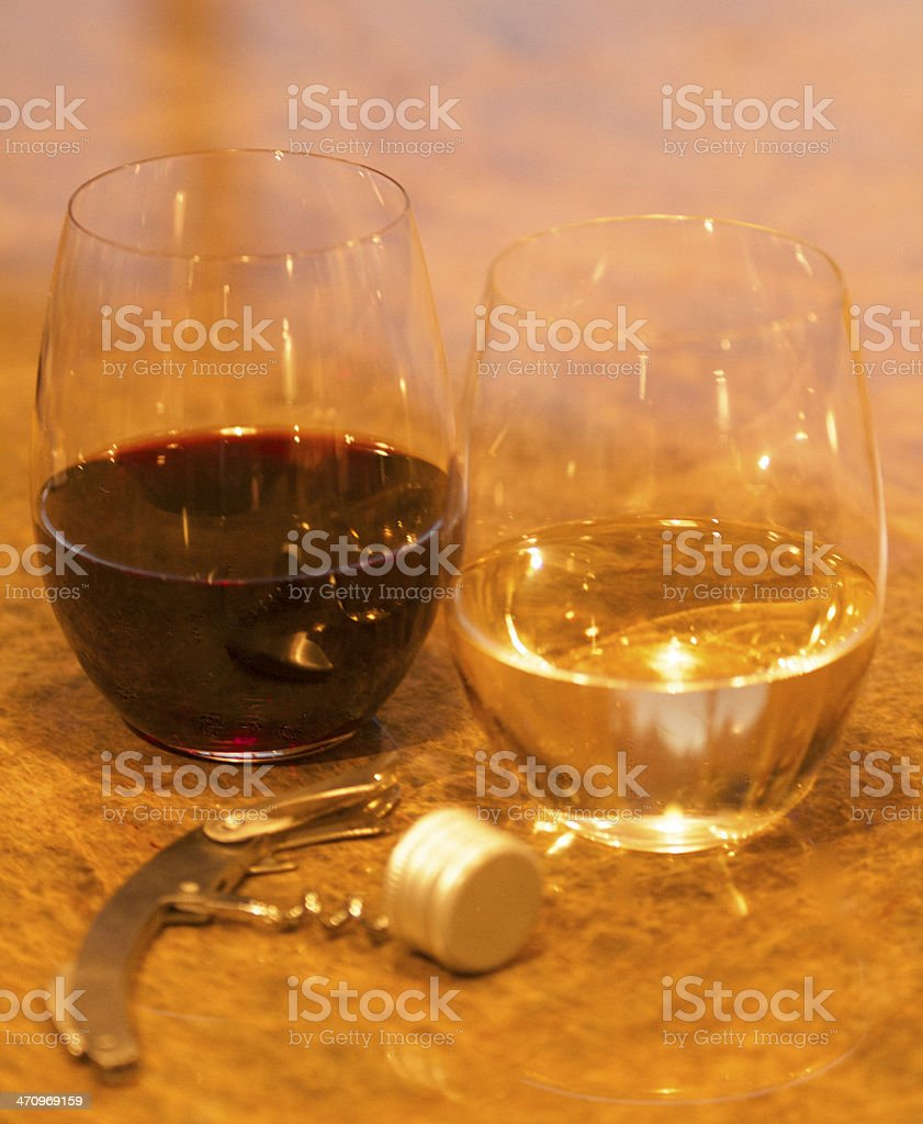 Glasses of wine with a corkscrew next to screw cap royalty-free stock photo