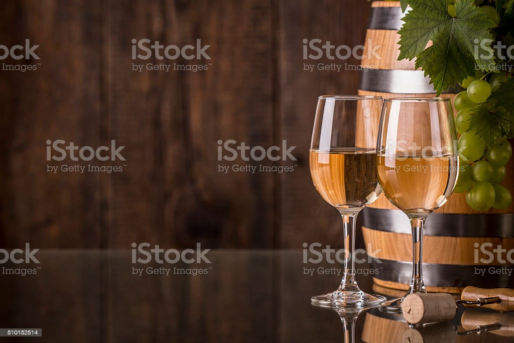Glasses of wine with barrel and grapes stock photo