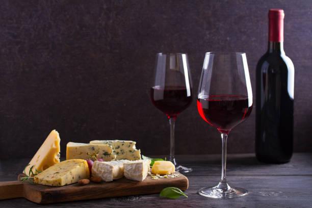Vasos de vino con queso, uvas y nueces sobre mesa de madera negra - foto de stock