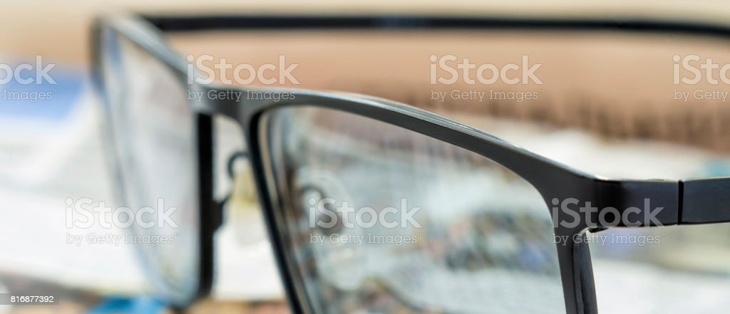 Glasses on a newspaper. Extreme close-up, selective focus. stock photo