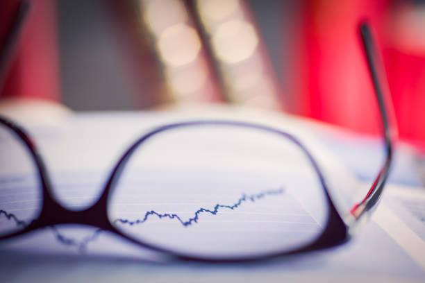 Brille auf einem Aktienchart – Foto
