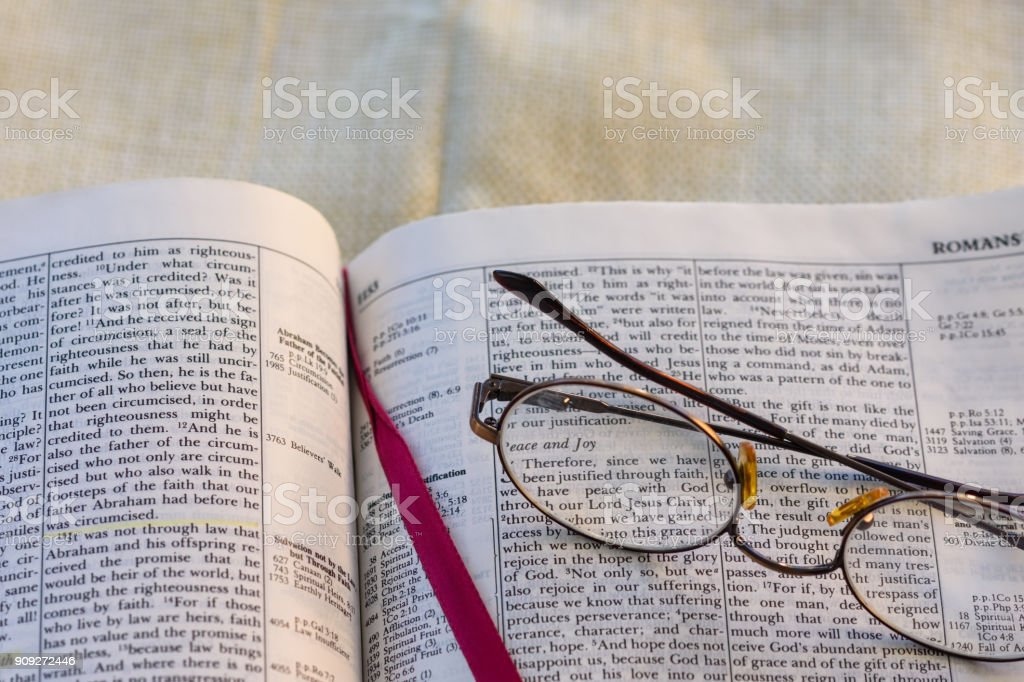 Bible pages open for study and education with old glasses resting on...