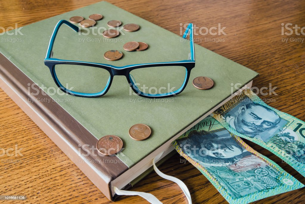 glasses on book and coins and australian dollar on desk stock photo