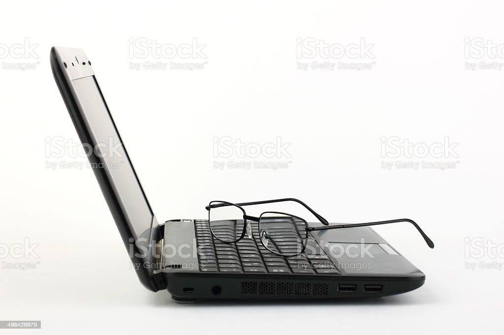 Glasses on laptop keyboard stock photo