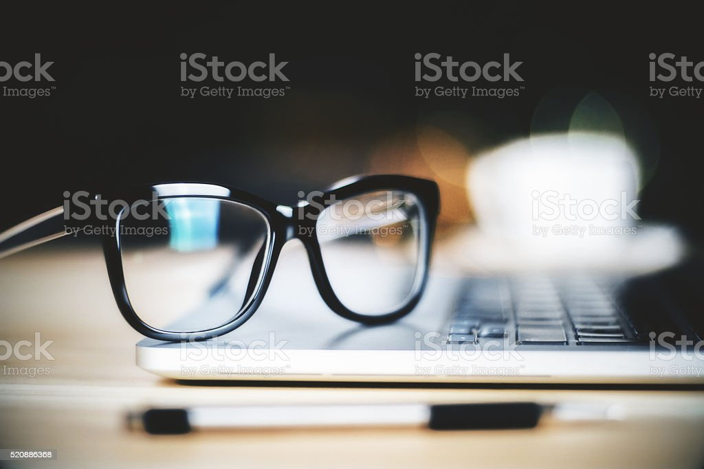 Glasses on laptop with pen, close up
