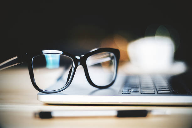 Glasses on laptop with pen, close up stock photo