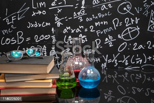 Glasses on old books and experiment bottle on a black table with a blackboard on the background.