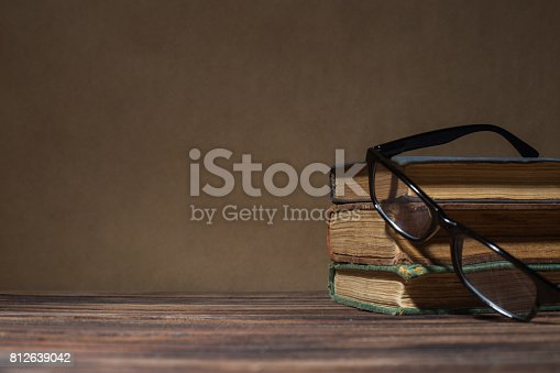 istock Glasses on Open Book, on Wooden Table 812639042