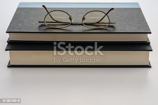 1034955096 istock photo Glasses on stacked books 913876818