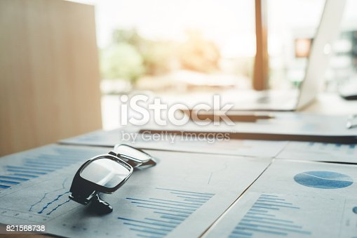 864278180istockphoto glasses on the business paper. Report chart 821568738