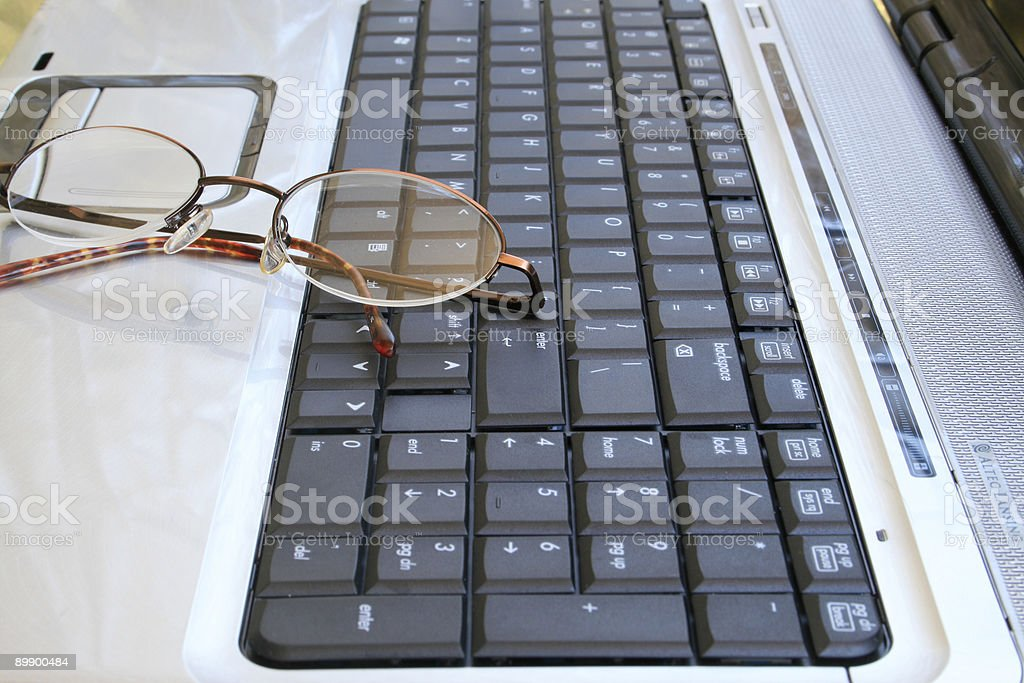 Glasses on the keyboard royalty-free stock photo