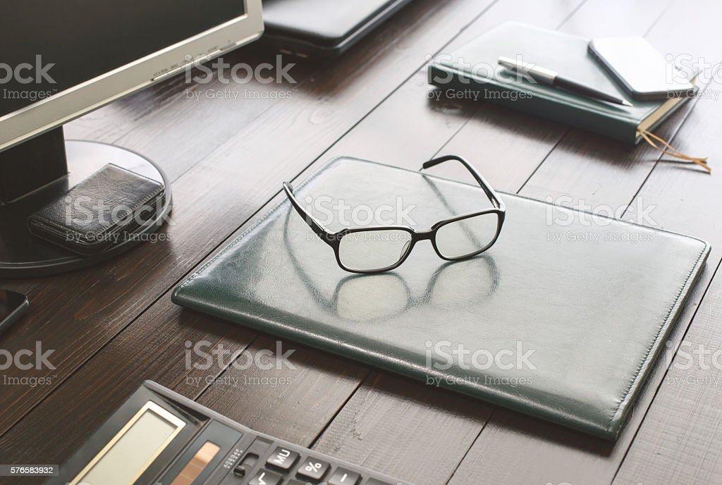 Glasses on the leather business folder on the office desktop stock photo