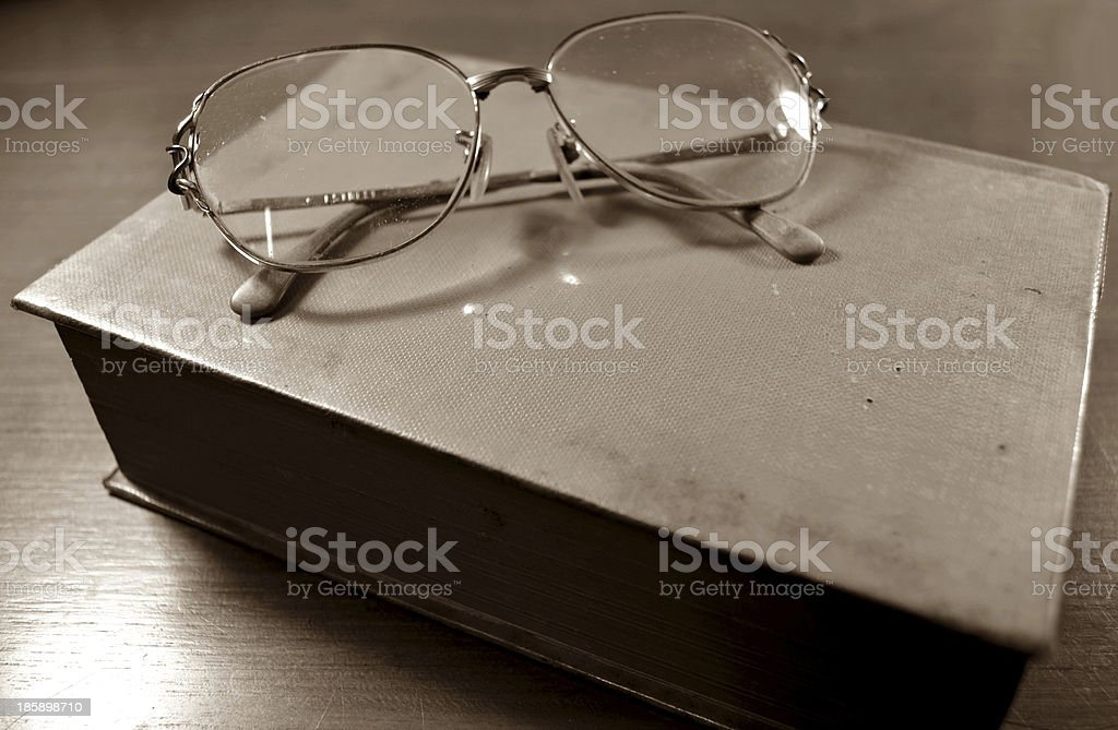 Glasses on the old book sepia royalty-free stock photo