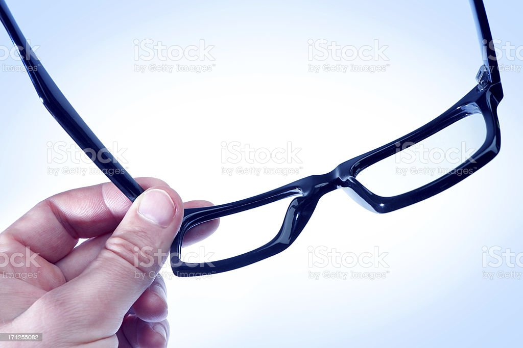 Glasses the hand of a man in blue tones. royalty-free stock photo