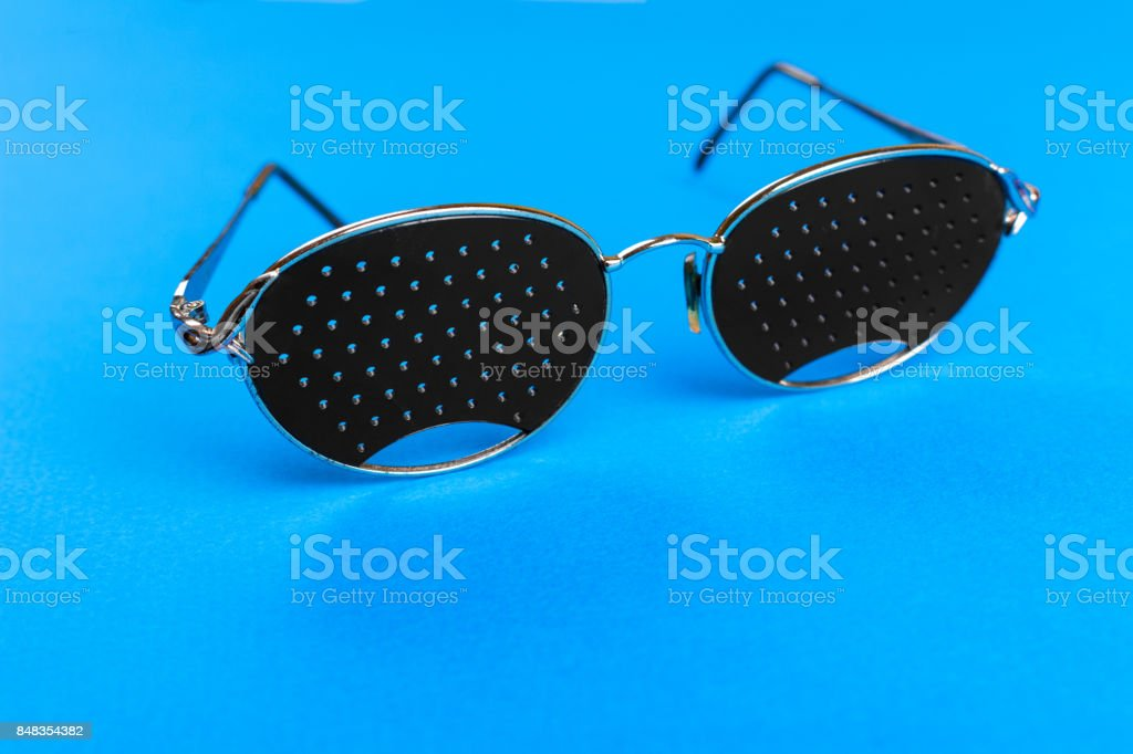 Glasses trainers. Black pinhole glasses on blue background. Medical concept. Top view. stock photo