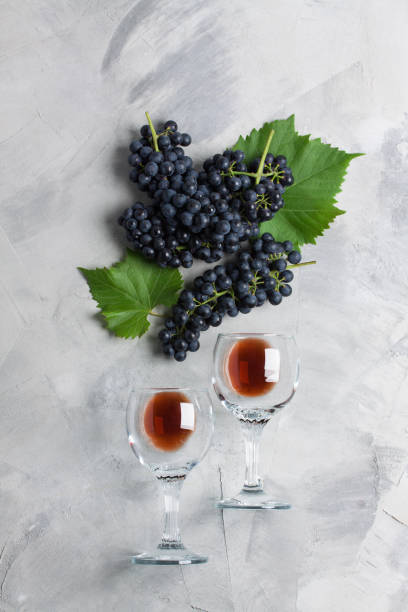 Glasses wine grape leaves concrete background top view flat lay Two glasses of wine, grape with leaves on grey concrete background. Concept wine from grapes,   brand or sommelier ads. Vertical orientation, top view, flat lay. cabernet sauvignon grape stock pictures, royalty-free photos & images