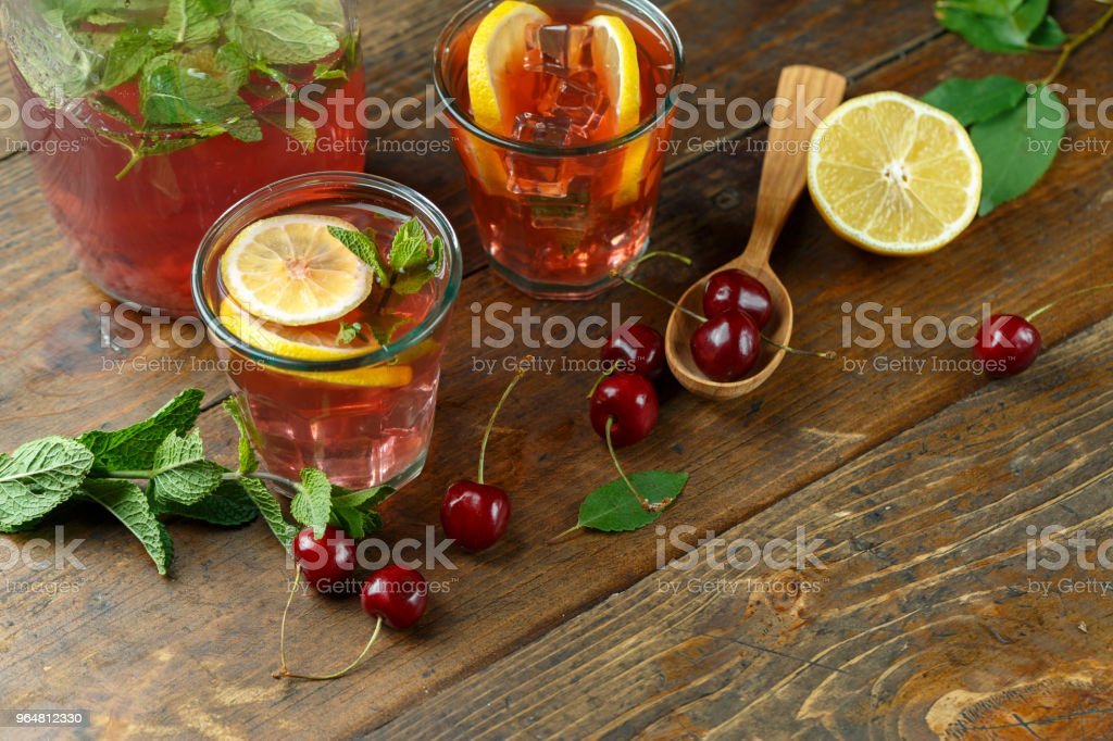 Glasses with a drink made of cherries on a vintage wooden background royalty-free stock photo