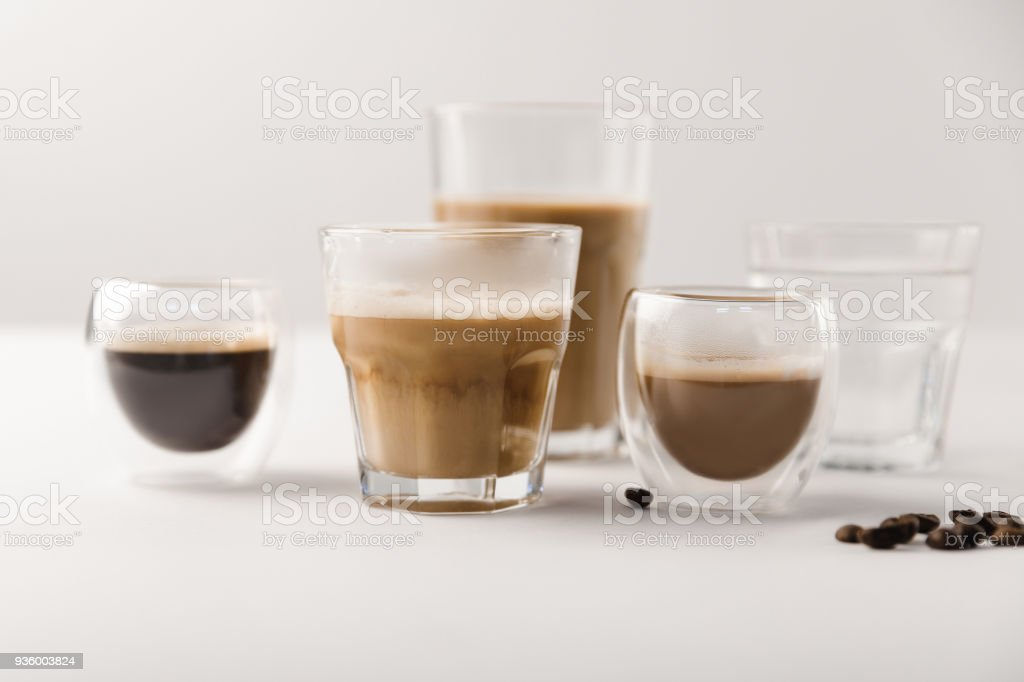 Glasses with assorted coffee drinks on white background with coffee beans stock photo