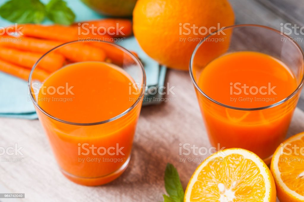 Glasses with carrot juice, apple, sliced orange and mint leaf royalty-free stock photo