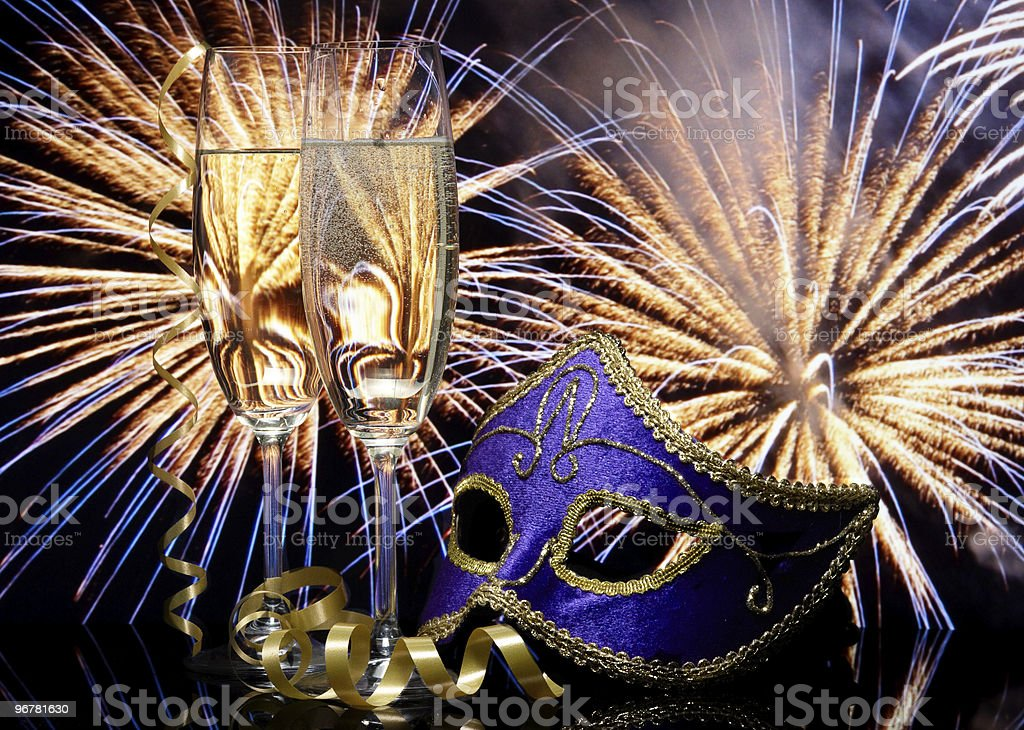 Glasses with champagne and Venetian mask against fireworks royalty-free stock photo