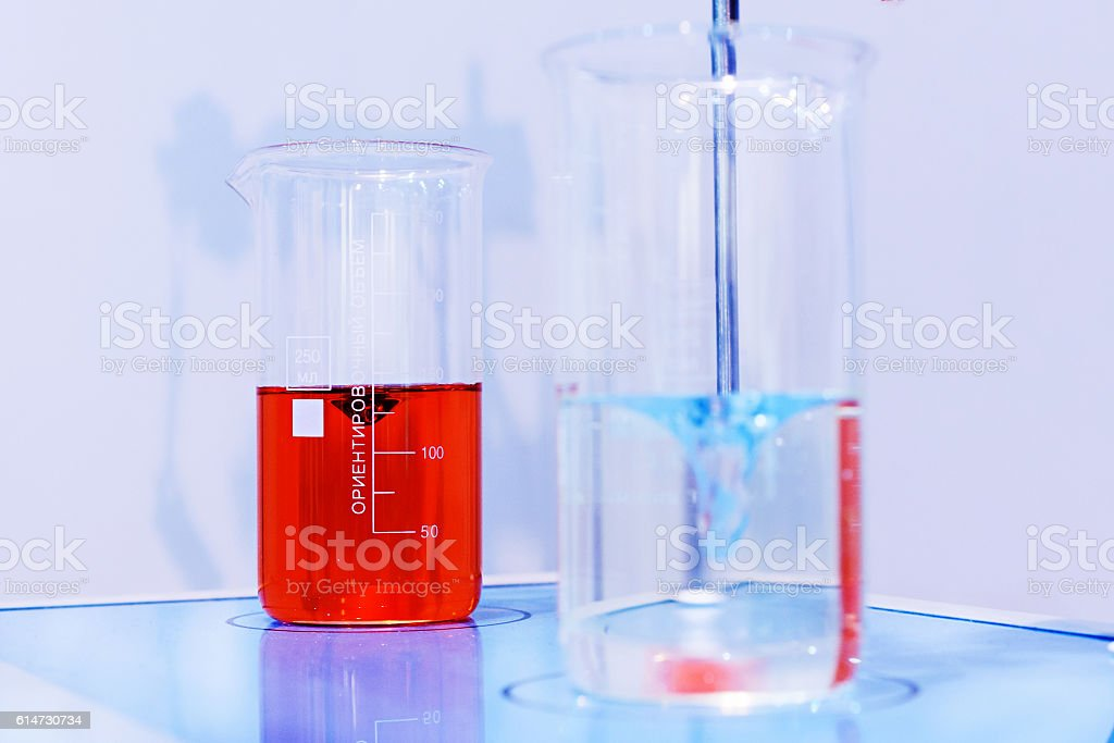 Glasses with chemical liquids are on a magnetic stirrer. stock photo