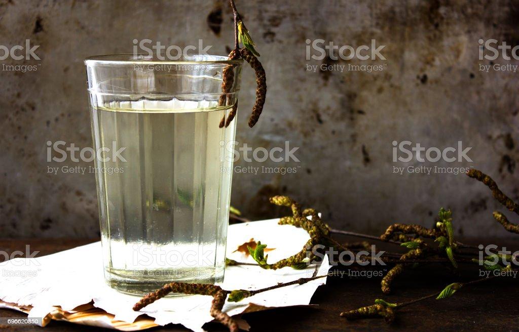 Bril met verse biologische detox berk water op grijze oppervlak foto