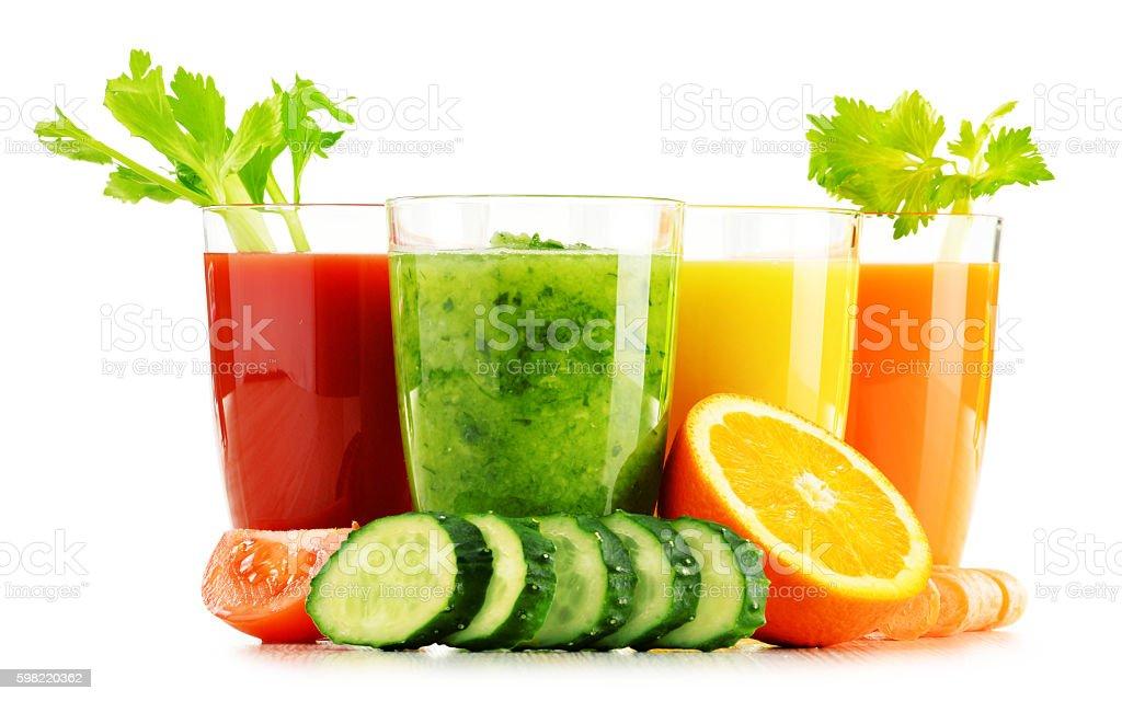 Óculos com legumes orgânicos frescos e sucos de frutas no branco foto royalty-free