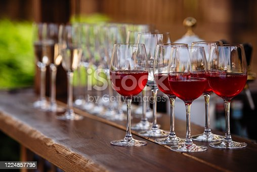 istock glasses with red wine, fruit drinks are poured into glasses, drinks are poured into glasses, clear glass is on the table 1224857795