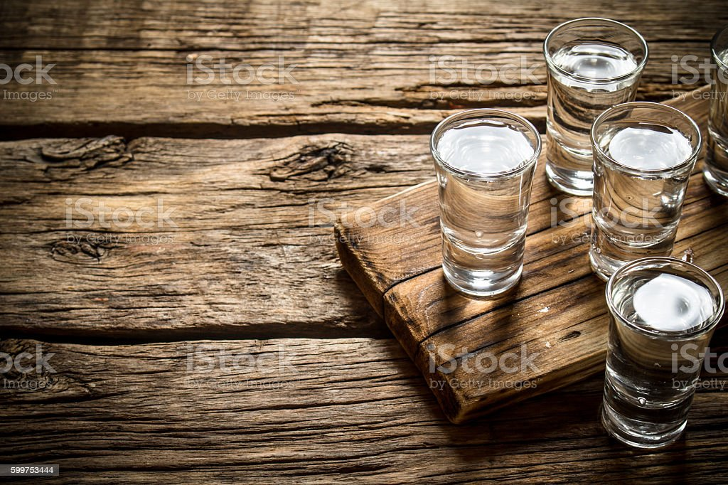 Glasses with vodka on the old Board. stock photo