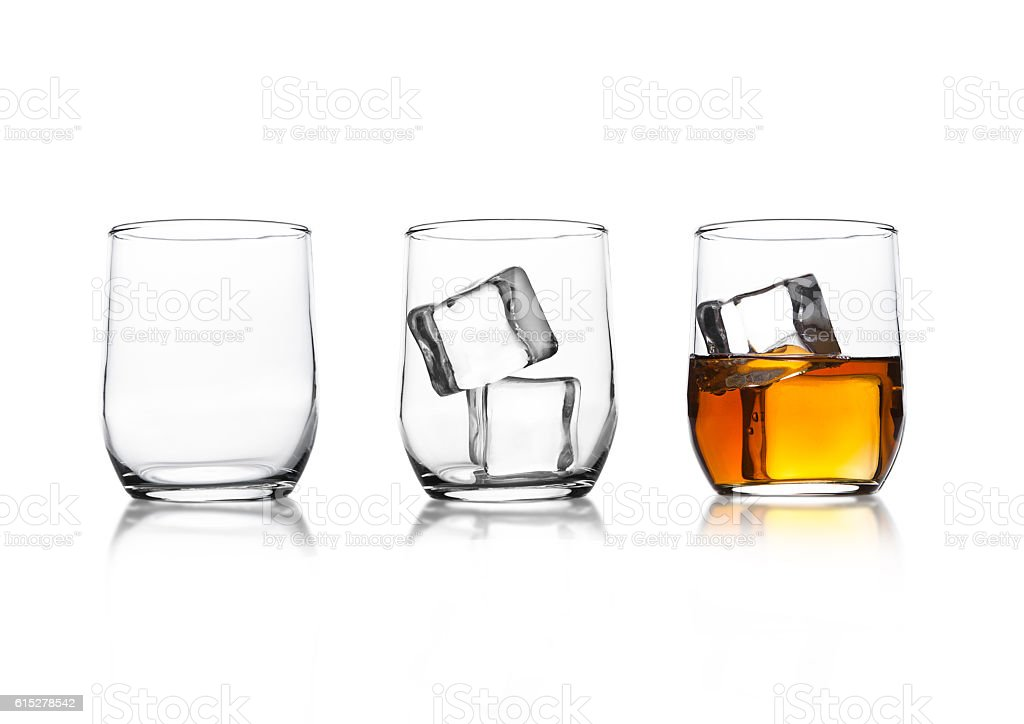 Glasses with whiskey and ice cubes and empty glass stock photo
