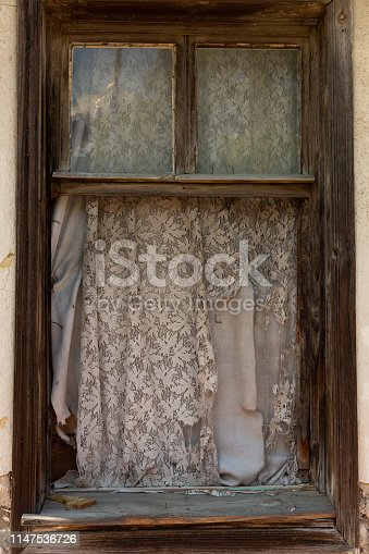 window with tattered curtains and no glass in an abandoned house in Edirne